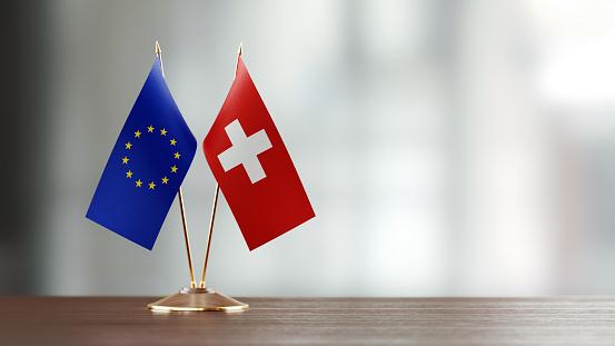 European Union And Swiss Flag Pair On A Desk Over Defocused Background - Fotografie stock e altre immagini di Accanto