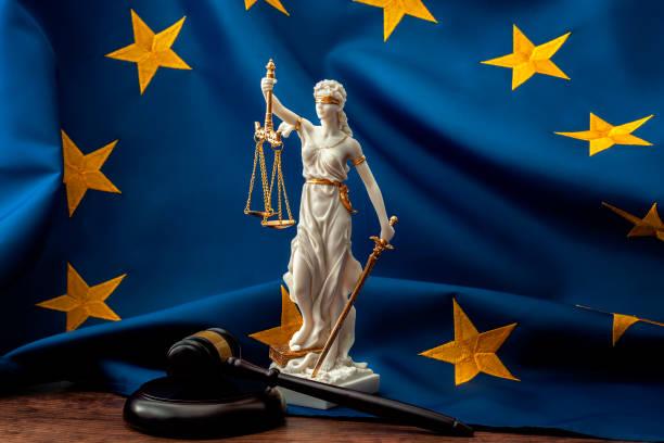 Tribunal de Justicia de la Unión Europea o TJUE, el sistema jurídico en Europa y la rama de la legislatura del concepto de gobierno con un mazo, una estatua de Themis la dama de la justicia y la bandera de la UE - foto de stock