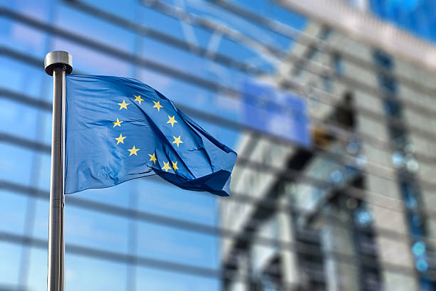 European Union flag against European Parliament European Union flags in front of the blurred European Parliament in Brussels, Belgium european commission stock pictures, royalty-free photos & images