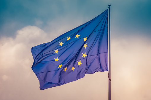 istock European Union flag flying the wind in sky, concept of unity between EU countries 1132960495