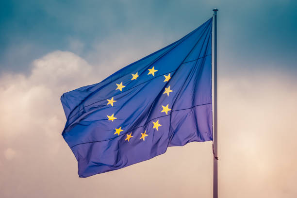 European Union flag flying the wind in sky, concept of unity between EU countries European Union flag waving in wind in colorful sky slightly cloudy. The official symbol of the EU. between stock pictures, royalty-free photos & images