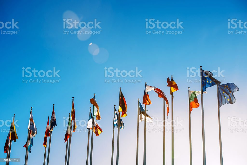 European Union flags against blue sky Flags in front of the European Parliament against beautiful blue sky in Strasbourg, Alsace, France Alsace Stock Photo