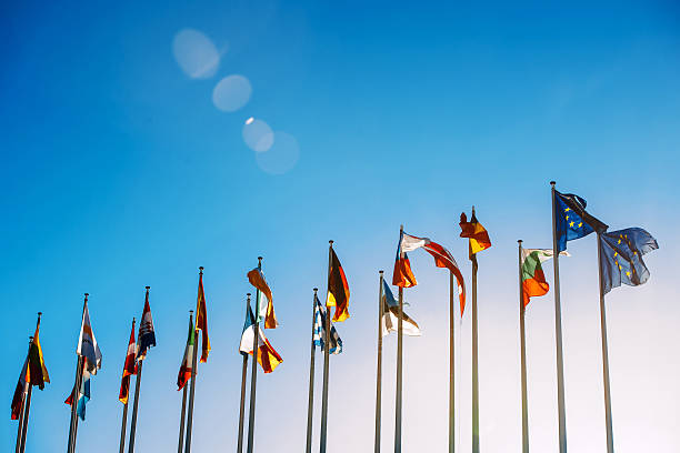 European Union flags against blue sky Flags in front of the European Parliament against beautiful blue sky in Strasbourg, Alsace, France european culture stock pictures, royalty-free photos & images