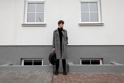 627398448 istock photo European urban young man in stylish autumn-winter outerwear with a fashionable leather black backpack in trendy boots stands on the street near a vintage wall. Handsome guy model in elegant clothes. 1199258747