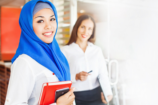 istock European woman and asian muslim woman standing in office room 491685000