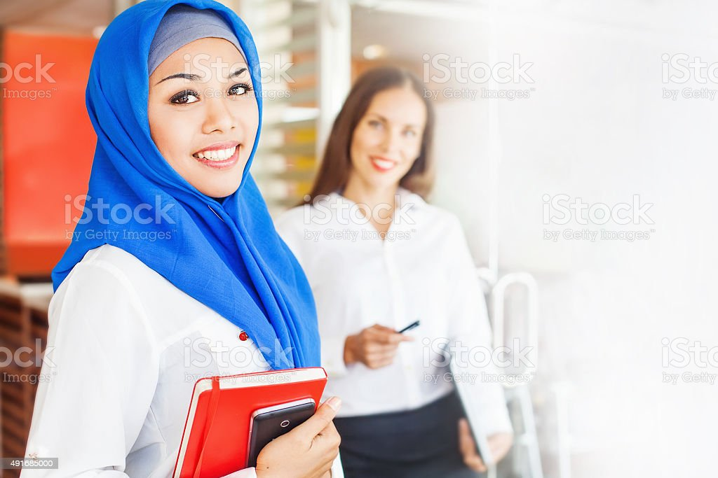 European woman and asian muslim woman standing in office room stock photo