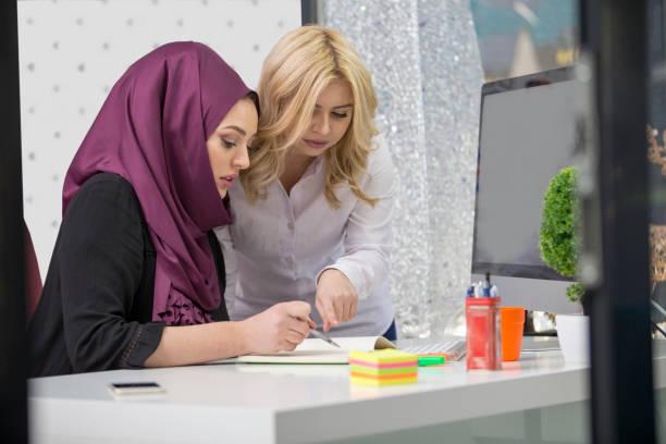 Mujer Europea y musulmana asiática trabajando juntos en el mismo proyecto - foto de stock