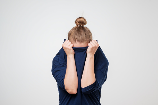European Woman Hiding Face Under The Clothes She Is Oulling Sweater On Her Head Stock Photo - Download Image Now