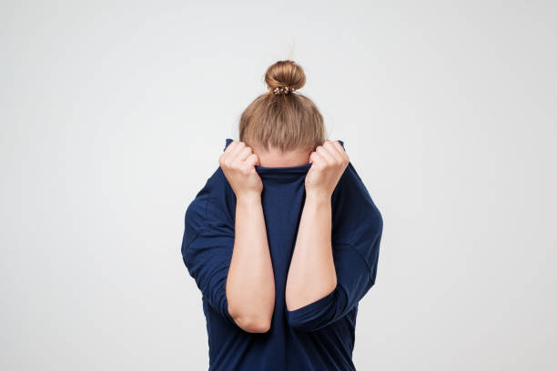 European woman hiding face under the clothes. She is oulling sweater on her head. stock photo