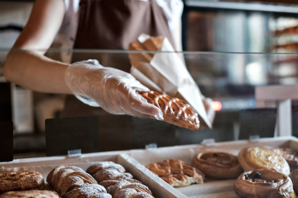 European woman sells in bakery putting bread in paper bag. stock photo