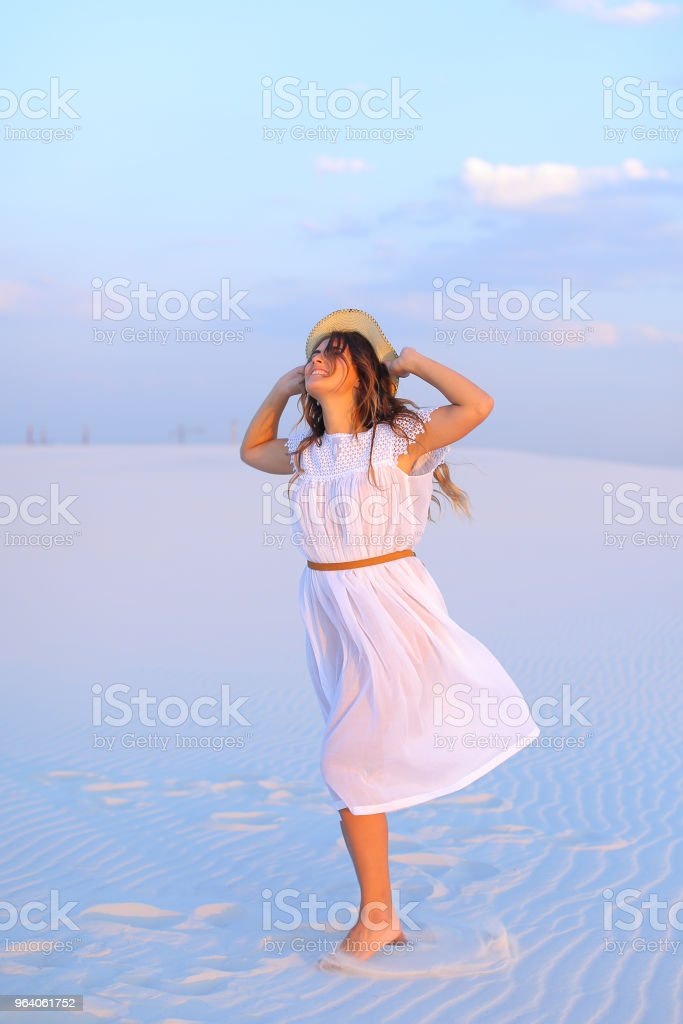 European woman wearing dress and hat standing on white sand in b - Royalty-free Adult Stock Photo