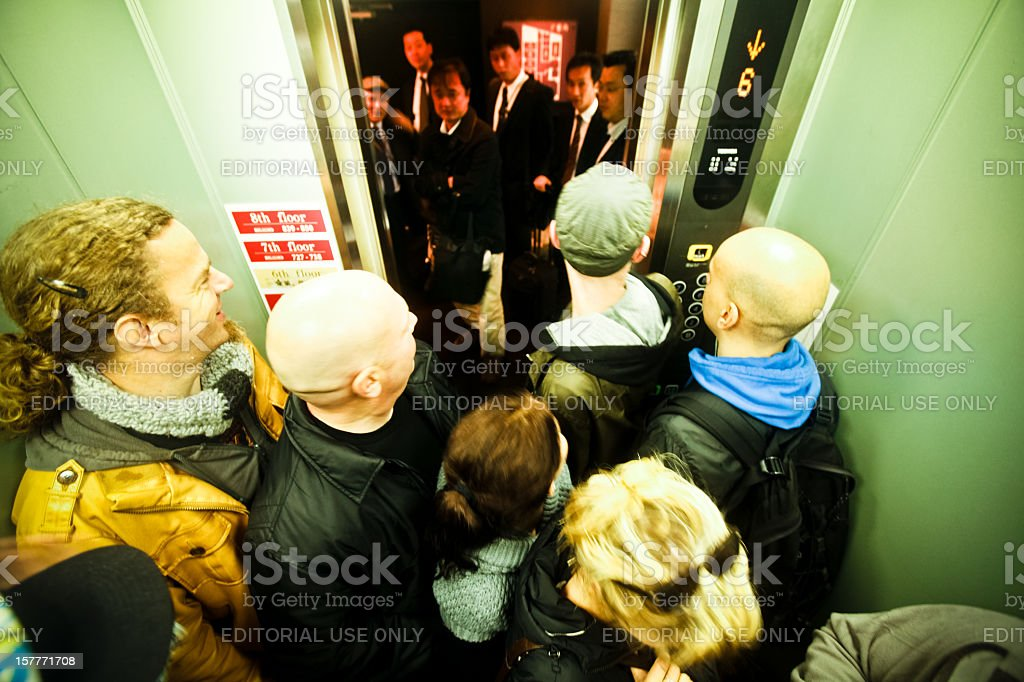 Europeans in elevator greet a waiting group of Japanese businessmen stock photo
