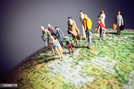 a collection of human figurines standing on a globe