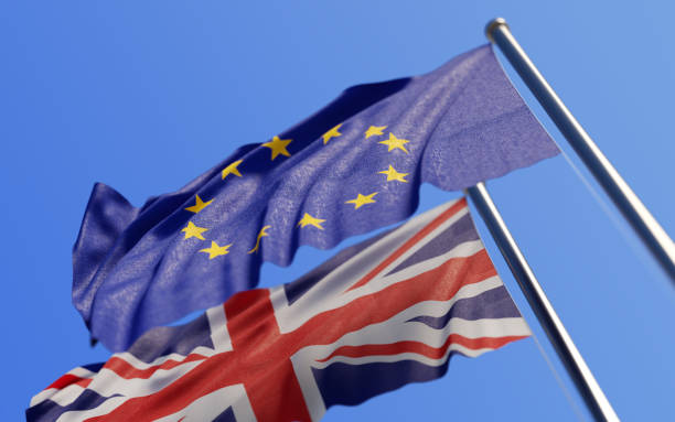 Europen Union And British Flags Waving With Wind On Blue Sky stock photo
