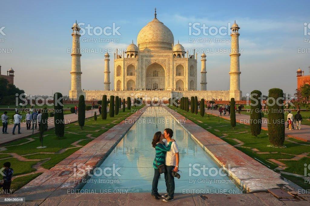 Europian man and young woman kiss in front of Taj Mahal stock photo