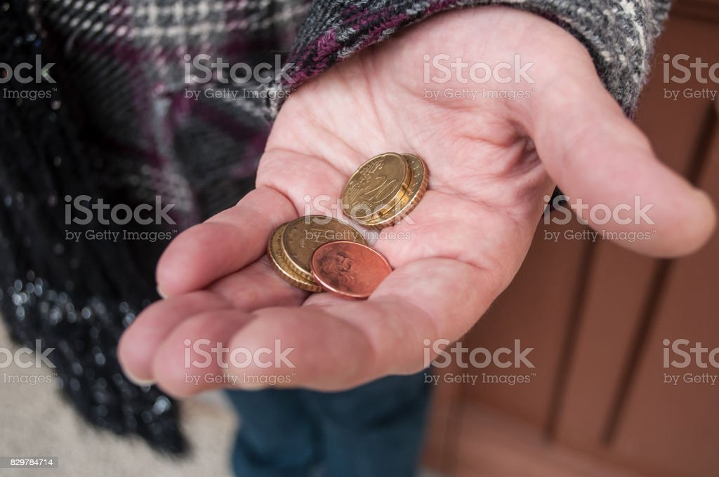 euros coins in hand of poor woman stock photo