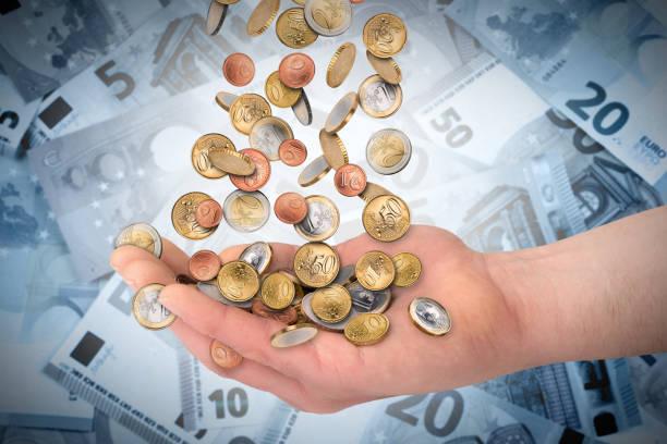 euzro münzen fallen in die offene hand - billigflüge buchen stock-fotos und bilder