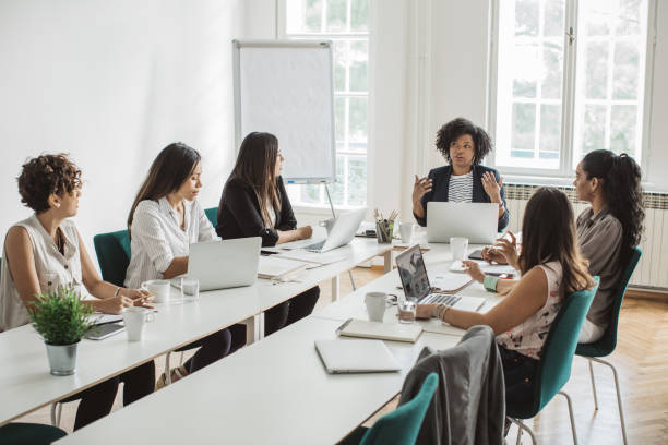 Evaluating new strategies Group of female latin women having a business meeting. Sitting at the table in conference room, working on laptops or making presentations. Taking selfies and posing for business portraits. market research stock pictures, royalty-free photos & images