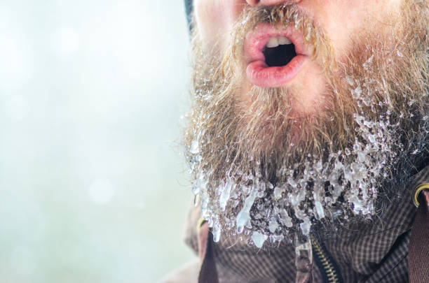 Evaporation from the mouth in winter Young man with a beard covered with icicles and frozen droplets on the street after exercise. Evaporation from the mouth in winter evaporation stock pictures, royalty-free photos & images