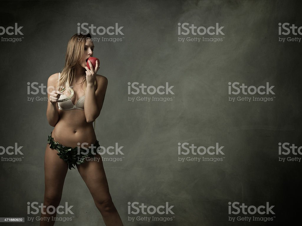 eve biting apple in a dark and abstract situation stock photo