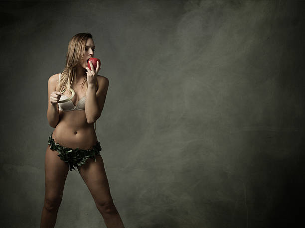 eve beißen einen Apfel in einem dunklen und abstrakte situation – Foto