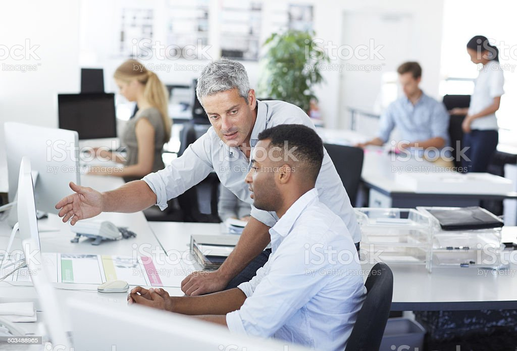 Even to fail is a learning experience Shot of two coworkers trying to figure out a problem together A Helping Hand Stock Photo