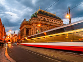 Evening at National Theater and blurred tram on the bridge, Prague, Czech Republic. Long exposure shot