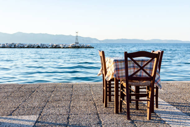 Evening at traditional Greek tavern, restaurant by the open sea Chairs and tables in typical outdoor Greek tavern in sunset light with shadows near wharf. high seat stock pictures, royalty-free photos & images