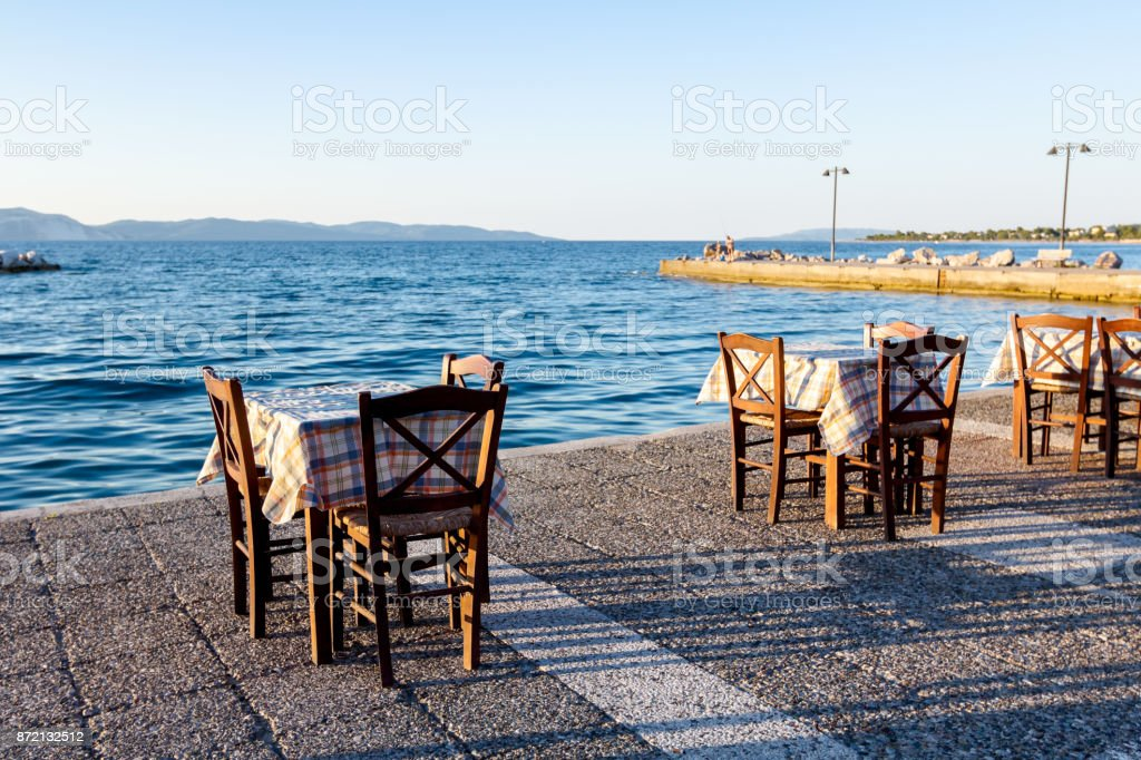 Evening at traditional Greek tavern, restaurant by the open sea stock photo