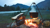Evening campfire during a camping trip. Cauldron on a burning fire. The tent is far away. Cozy Hiking evening of travelers by the river.