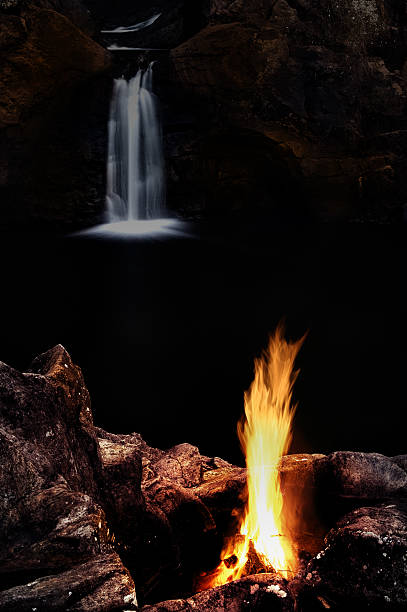 Evening campfire on a riverbank besides a waterfall in Australia stock photo