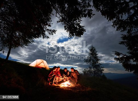 istock Evening camping in the mountains. Friends are sitting around fire with beer enjoying holiday 941352688