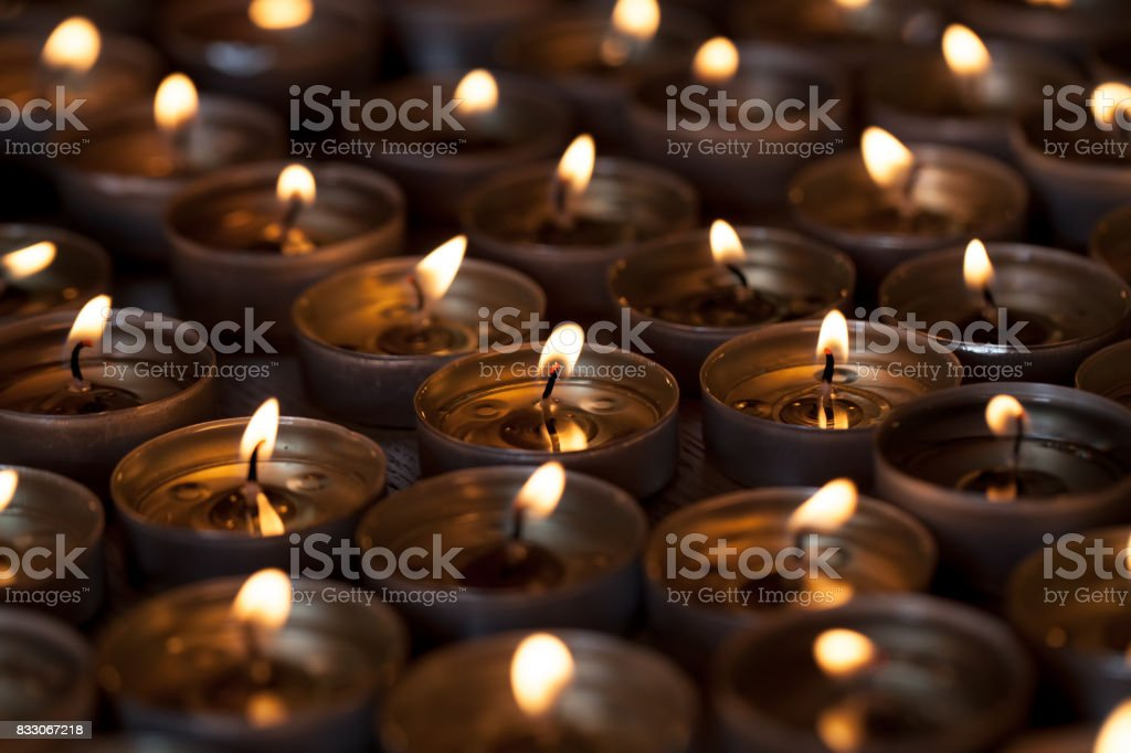 Evening candlelight from multiple lighted tea light wax candles. stock photo