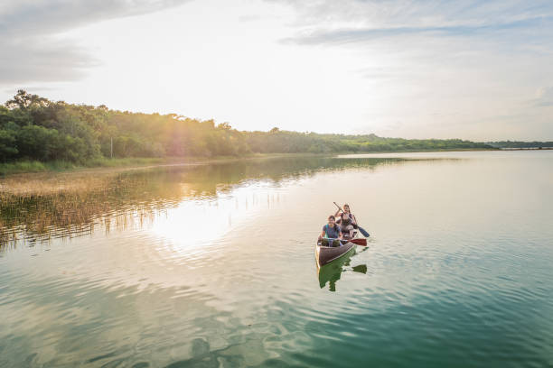 Evening Canoeing, Millennial Multi-Ethnic Sisters Paddling in Lagoon Nature Reserve stock photo