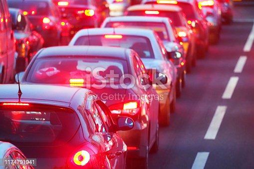 Evening, city traffic jams, street road. Standing in a row cars, rear view, red stop lights. Dividing strip