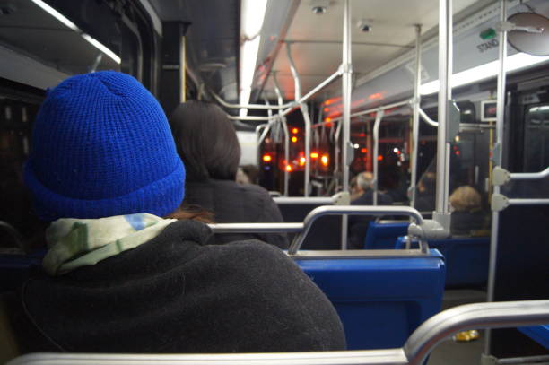 Evening commuters ride a bus at night stock photo