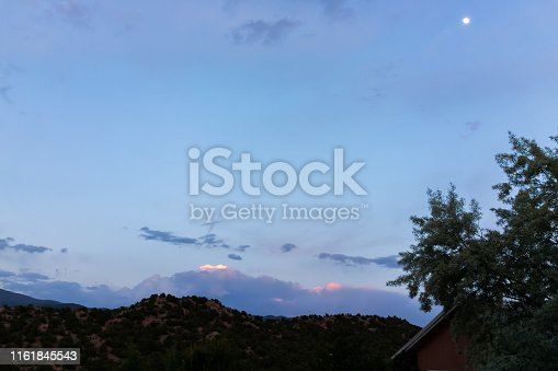 Evening dark night in Santa Fe, New Mexico mountains in Tesuque community neighborhood house with moon in twilight and house