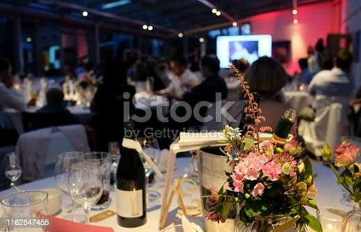 Evening event with flowers and wine bottles on the tables