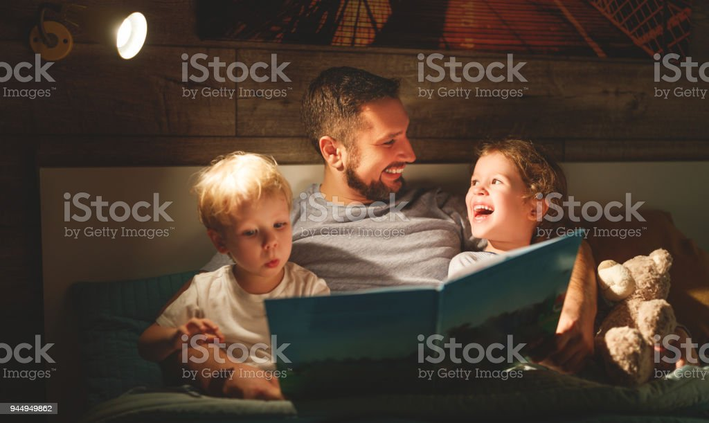 evening family reading. father reads children . book before going to bed stock photo