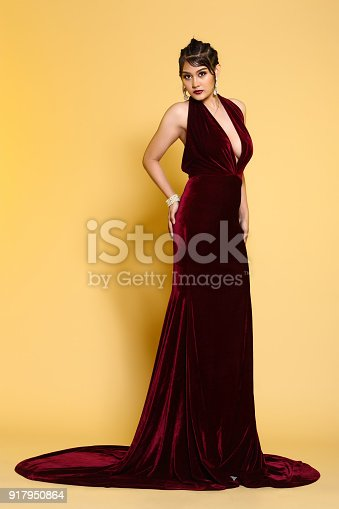 Red Velvet Evening Gown Ball Dress in Asian beautiful woman with fashion make up black hair, High Heel shoes, studio lighting beige yellow background. Concept luxury to join social night event