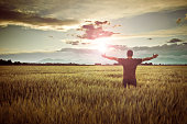 Man standing in a wheat field contemplating the sunset.