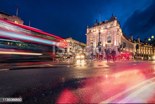 Long exposure photo with evening illumination at Piccadilly Circus in London city during blue hour on a rainy English evening. Crowd and traffic with motion blur due to the exposure time with unrecognisable accidental commuters and tourist. Image has copy space and it is ideal for background. Shot on Canon EOS R full frame system.