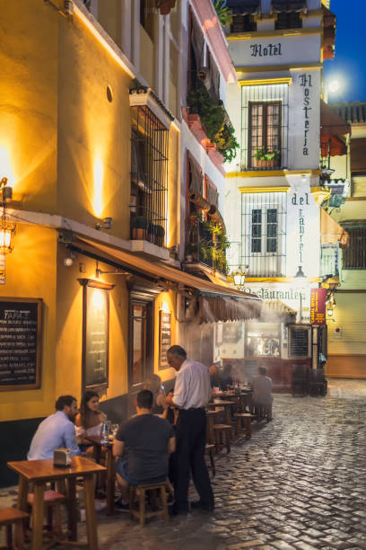 Evening in Santa Cruz, Seville A restaurant with guests in the evening in the popular historical Santa Cruz neighborhood in Seville, Spain. santa cruz seville stock pictures, royalty-free photos & images