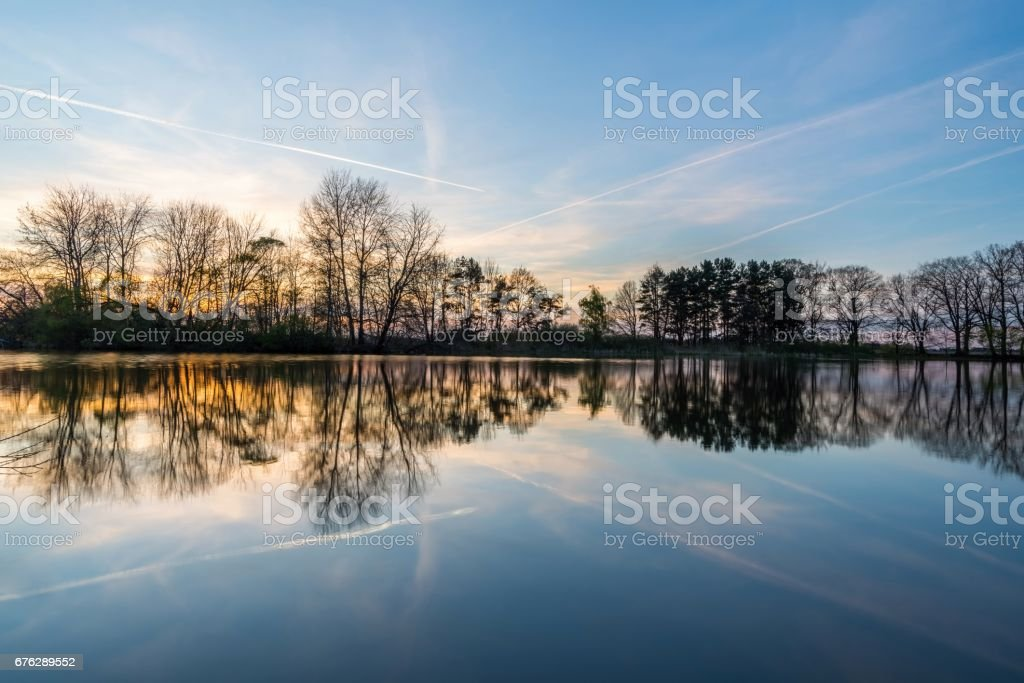 Evening landscape with several trees on side of pond stock photo
