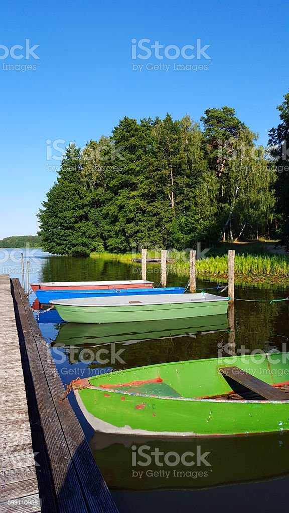 evening light at lake with boats and jetty stock photo