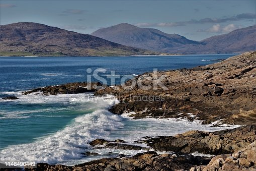 A series of 8 stunning images of evening light over the spectacular beaches of West Harris, on the island of Eilean Siar in the Western Isles or Outer Hebrides off North West Scotland. The images were all taken in late evening in April at an approximate latitude of 58 Degrees North, where the angle of Northern sun at close proximity to the Arctic Circle gives an unusual and dramatic colour spectrum to the images. This seventh image is looking due North over dramatically breaking North Atlantic Rollers with attendant spray and surf, over towards Taransay. The North Harris Hills (actually mountains) are clearly visible with the peak of An Clisham, the highest mountain on the Western Isles at over 3000ft, being front and centre at the vanishing point of the image.