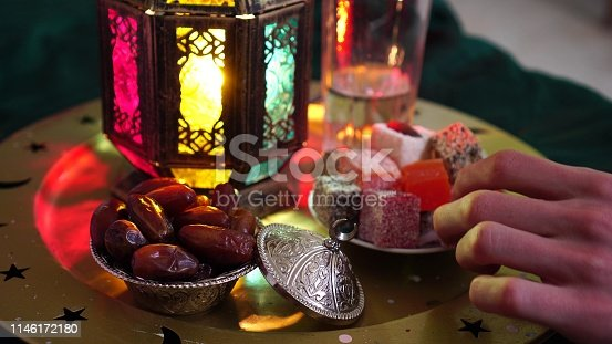 A young man prays and drinks water and eats dates. Evening meal during the Holy Muslim month of Ramadan