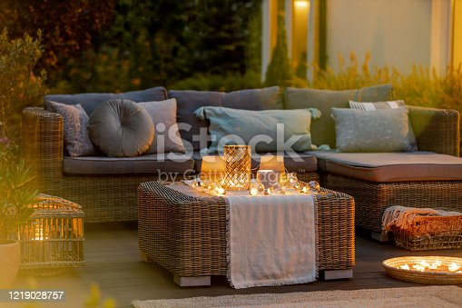 Evening on a modern designed cozy terrace with sofa and coffee table