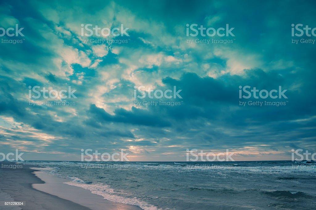 Evening on the beach. Dramatic cloudy sky over sea stock photo
