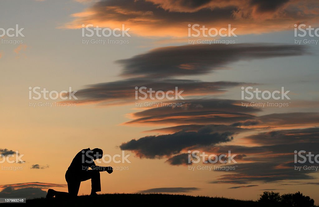 Evening Prayer Silhouette of Unrecognizable Man Kneeling stock photo